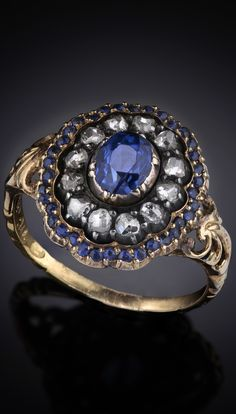 Ring in 18 K gold and silver with a large light blue sapphire, rose-cut diamonds and smaller sapphires.