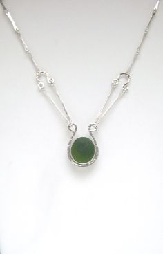 The dark green sea glass is genuine. It was found on a beach in England and is no back bezel set. The necklace is handmade of round sterling silver
