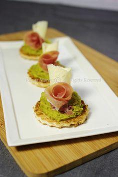 Crostini con crema di piselli, roselline di prosciutto e scaglie di parmigiano