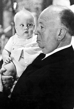 Alfred Hitchcock holding a baby on the set of 'The Birds', 1963.