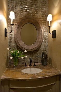 Tiled wall behind round mirror. Very elegant for a small bathroom