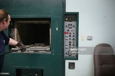 Crematorium technician Jonathan Prideaux scrapes ashes and bones from a cremation oven at St. John's Norway Cemetery and Crematorium on June 17, 2015. At times, remains go unclaimed, into a cardboard box and remain in unmarked niches or unmarked burials until claimed.