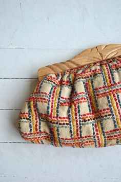 Vintage 1940s oversized clutch of woven wool/cotton with vibrant criss cross design of red, orange, yellow blue shades. Chunky carved wooden kiss closure and fully lined interior. --- M E A S U R E M E N T S --- 19 x 9 maker/brand: n/a condition: excellent ➸ More vintage bags http://www.etsy.com/shop/DearGolden?section_id=10308208 ➸ Visit the shop http://www.DearGolden.etsy.com _____________________ ➸ instagram | deargolden ➸ twitter | d...
