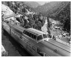 "The superb Vista-Domed streamliner, ""California Zephyr"", rolls over Western Pacific rails through Feather River Canyon in California, circa 1960. Mountains and a river are in the background."