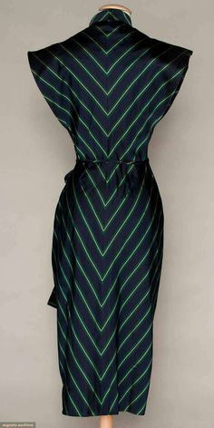 Dinner dress of ribbed navy, green & yellow striped silk, shawl collar to low V neckline, short double winged sleeves, wrap sarong-style narrow skirt, attached self fabric cord belt,