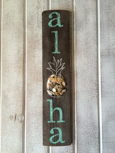 Aloha sign with the o made to look like a pineapple. I filled the center of the pineapple with crushed shells and beach pebbles I found on the beach. Find this and many more hand painted signs at my etsy store~SummerSunSign.