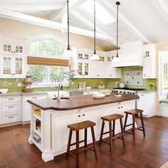 Open layout kitchen with a wood-topped island, green glass subway tile, an oversize window, and a soaring ceiling with skylights.