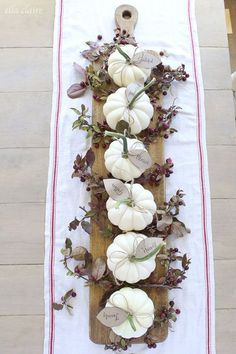 Elevated on a wooden paddle, minipumpkins stand out in a major way. Tuckgreenery between each one, and tie on tags with festive phrases.Click to find out how to do it yourself and for more easy and stunning Thanksgiving centerpieces that will amp your dinner table this year.