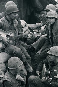 19 Feb 1968, Khe Sanh, South Vietnam --- Marine Cpl. Bruce Lint (L) of Meriden, Connecticut and another Marine (unidentified) provide a little musical entertainment for fellow leathernecks at this fortress in northwestern south Vietnam. A radio operator and interpreter with a reconnaissance unit, Cpl. Lint isn't practicing his trade much recently. since the North Vietnamese have Khe Sanh almost surrounded, any recon outfit travelling very far would risk capture. --- Image by ©…