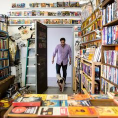 """Ash Kalb, a co-founder of the vintage science fiction bookstore Singularity & Co., enters the store with his dog, Robot. The store is the happy accident of a successful Kickstarter campaign to """"Save the SciFi!"""" (Photo: Karsten Moran for The New York Times)"""