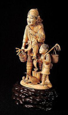 A very large and fine ivory okimono of a fisherman and his child Meiji period (1868-1912) carved wood stand. Height 37 cm, 45.5 cm overall