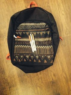 DIY Aztec pattern back pace. Buy plain black backpack and metallic sharpies draw on backpack.