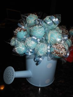 Baby boy cake pops in a watering can for a baby shower.