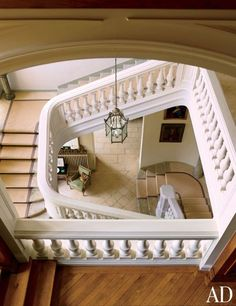 A jute-bound wool runner lines a stone staircase; the lantern is 19th-century French, and the armchair is vintage Jansen.
