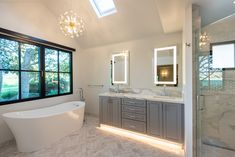 This Carmel Valley bathroom remodel features a deep soaking tub and walk-in shower with detachable showerhead and offset controls. A skylight and windows throughout bring plenty of natural light in. Stone countertop with underlit vanity fitted with LED light mirrors for perfect lighting.