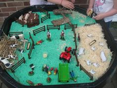 Farm Sensory table. Wood shavings for the sheep, brown playdoh for the pigs, & straw for the cows.