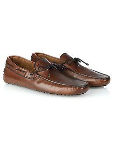 Artigianalità e tradizione sono le caratteristiche chiave per l'iconico mocassino Gommino Tod's in pelle con finitura brunita. Il laccetto frontale in cuoio intrecciato Tod's aggiunge un tocco distintivo a questa scarpa senza tempo.