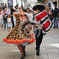 A couple dances Cueca in the streets of Concepcion, Chile. Is a family of musical styles and associated dances from Argentina, Chile and Bolivia. #biobio #celebration #chile #china #concepcion #costume #country #couple #cueca #culture #dance #dancers #dancing #dress #expression #folklore #hat #hispanic #huaso #latinamerica #nationalism #party #performers #poncho #southamerica #street #traditions #typical