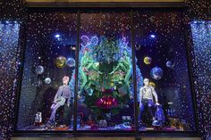 """Harvey Nichols and Fortnum & Mason have revealed their Christmas windows, with both stores opting for festive-inspired scenes bursting with colour, sparkles and glitter. Window designers at Harvey Nichols, left, used at least a million flakes of glitter, more than 300,000 sequins, 15,000 gift boxes, 540 baubles and 620 mirror balls to create the scenes, under a loose theme of """"disco-glam"""". The look isinspired by Studio 54, the partywear trend of the season."""