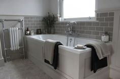 Traditional bathroom furniture looks great with these grey subway tiles and white grout. Upstairs Bathrooms, Grey Bathrooms, Bathroom Renos, Bathroom Interior, Grey Bathroom Tiles, Bathroom Vanities, Grey Bathroom Decor, Tiled Bathrooms, Boy Bathroom