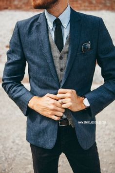 Something as simple as teaming a dark blue sportcoat with black jeans can potentially set you apart from the crowd. Shop this look for $129: http://lookastic.com/men/looks/blazer-waistcoat-tie-long-sleeve-shirt-jeans-belt/7438 — Navy Blazer — Grey Plaid Waistcoat — Black Tie — Light Blue Long Sleeve Shirt — Black Jeans — Dark Brown Leather Belt