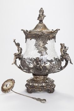 WMF (Wurttembergische Metallwaren Fabrik) German  Monumental Classical style plated silver and cut glass centerpiece-punch bowl with lid and shell form ladle, applied two mythological figural handles and two putto to a footed, reticulated and repousse base, fitted glass bowl cut with baskets of flowers and silver plated mount at top, the lid having female bust finial, marked ladle, circa 1900 #decorativearts #silver   www.linkauctiongalleries.com Glass Centerpieces, Wmf, Bowl Cut, Flower Basket, Cut Glass, Punch Bowls, Metal Working, Silver Plate, Art Decor