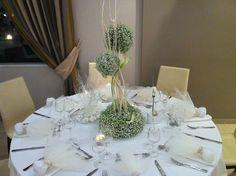 Στολισμός ροτόντας σε λευκό με κεράκια και στο κέντρο, μια ψηλή σύνθεση με κλαδιά και φρέσκα λουλούδια.