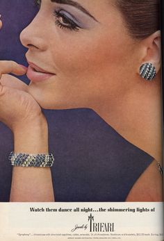 "1965 - TRIFARI - ADS - ""Symphony Collection"" - Watch them dance all night ... the shimmering lights of Jewels by Trifari. ""Symphony"" ... rhinestones with simulated sapphires, rubies, emeralds. Or all rhinestones. Necklaces and bracelets, $12.50 each. Earrings, $6.00. Jewelry designed copyrighted: Trifari, Krussman and Fishel, inc."