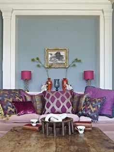 Prestigious Textiles -  Eclipse Fabric Collection - A wood coffee table with a pale lilac sofa and luxurious purple, blue and silverplain, patterned and textured cushions