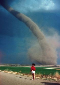 Audra Thomas posed as an F1 tornado swirls a mile away towards her family farm; the devastating tornado later destroyed buildings on her...