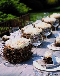 Large, open peonies settle into nests of twisted fern vines. Inside each basket is a shallow plastic bowl of water (for extra stability, use a wire grid to hold stems in place). A smaller nest atop the napkin at each place holds a more closed flower; its stem sits in a water tube concealed within the nest.