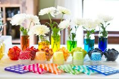 flower vases filled with colored water and fruit in a rainbow of colors