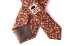 MOSQUITO HAWKS - Exuding a sense of power and poise, Dragonfly's are an important and beautiful insect. Designed with the warm detail colours of beige, orange and red, this tie is set on brown background. Dragonfly's help keep our Mosquitos at bay and create an environment that is safe and important to them, an important factor in the office.