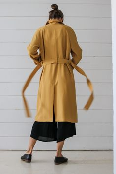 Double-breasted trench coat with a reglan, wide sleeve. Created on the basis of the Oslo model. It has an asymmetrical flap in the front. Fastened with buttons and tied with a belt in waist. On the sleeves there are straps with buttons. The coat has the form of the letter A, it is not fitted. Made of thick rayon fabric on a viscose lining.