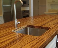 Zebrawood  Aptly named for its striking stripes, zebrawood is commonly used as a home accent. But this beauty is also a beast. It will stand up against almost anything you throw at it, all while adding an unmistakable 'wow' factor to your kitchen.