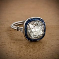 A stunning Vintage Cushion Cut Diamond Engagement Ring surrounded by a halo of Sapphires and set in a beautiful handmade platinum setting.