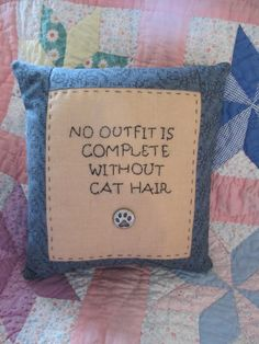 "A 8"" x 9"" pillow is trimmed in calico. The fun message is hand-embroidered on muslin with a paw button."