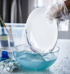 O rebordo acabado de pintar de um prato FÄRGRIK da IKEA e que está a ser mergulhado numa tigela com água