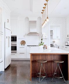 """Tiles:  Another bistro-inspired touch was her choice of dark honed-limestone tiles for most of the main floor. """"The tile grounds the space since there's an abundance of white everywhere,"""" Tanya explains. """"And it's proven great for hiding dirt."""""""