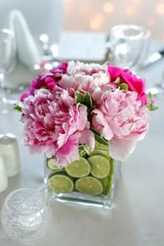 love the cut up limes in the vase with these pretty pink flowers