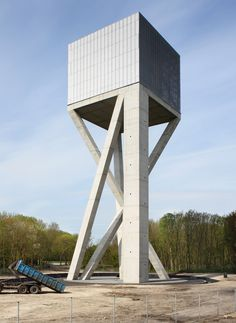 Belgian architecture studio V+ has completed a mesh-covered water tower that is supported by angled concrete columns