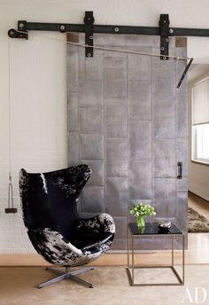 An industrial-chic Manhattan loft is outfitted with a black-and-white Jacobsen Egg chair.
