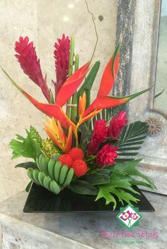 The warmth of the tropics is brought to life in this stunning arrangement of heliconias, gingers, novelty and premium greens. Designed in a low black container.