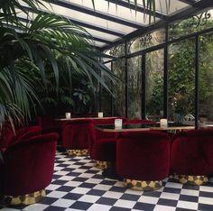 La verrière du Très Particulier, bar à cocktail situé à l'Hôtel Particulier Montmartre. velours rouge, sol en carreaux de ciments, plantes tropicales Architecte d'intérieur Pierre Lacroix