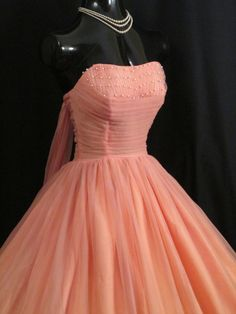 Graceful Vintage 1950's party/prom dress in a gorgeous shade of romantic coral pink chiffon! Features a ruched (boned) chiffon bodice studded with pearls, rear sash treatment, and of course the wonderfully full tea length skirt, perfect for dancing.