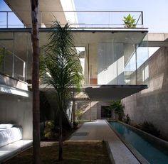 Dividida em dois níveis, a parte destinada à moradia é acessada por uma escada de concreto que leva à varanda. Dali, chega-se à cozinha e ao living, cuja integração com a natureza se dá pela abertura total da porta de vidro deslizante. No nível inferior, os dormitórios são amplos, com mobiliário minimalista. Os traços arquitetônicos de tão exatos não carecem de muitos acessórios, eles bastam por si só. Projeto SPBR Arquitetura