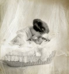 A heartwarmingly precious moment shared between a young Edwardian mother and her sleeping child.
