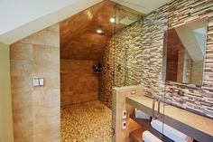 A continuous wall of glass and stone mosaic tiles seamlessly give the illusion of a larger space. A custom lavatory and steam shower with pebble flooring gives a subtle foot massage while heated floors add to the hotel like bath. http://www.nspjarch.com/