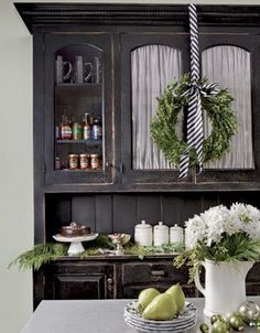 """The black and white theme from one of our front door wreaths is carried in to this country kitchen""."