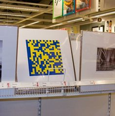 "'On Black Friday, Bay area artist Michele Pred infiltrated her local IKEA and dropped off ten framed prints sealed and ready for purchase. All ten prints were sold by the end of the day. The prints feature a QR Code image in IKEA's trademark blue and yellow. When scanned by a mobile device, the code takes the viewer to a webpage that says simply, ""you are what you buy.""'"